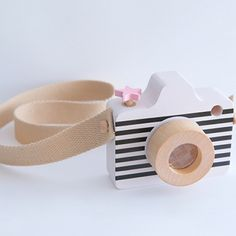 Super stylish wooden camera by Kukkia Toys. Featuring a black and white body with a pink star button at the top, a rotating lens and a fabric strap. We thing the perfect little accessory for any budding photographer! Made from Beech Wood Made in Japan
