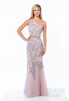 One shouldered tulle prom gown with an assymetric neckline and mesh cut out at the waist. it is detailed with all over crystal embellishment and fluted mesh at the hem