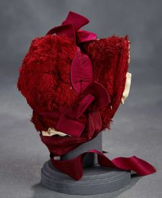 "The soft burgundy plush velvet bonnet has cap back with ruffled brim, burgundy bow and streamers, and is lined with triple tiers of ivory silk ruffles. 5 1/2""h. 2 1/4"" inside head width. Circa 1880."