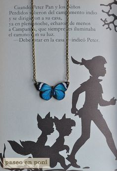 A bright blue butterfly necklace with a desing on laser-illustration wood.