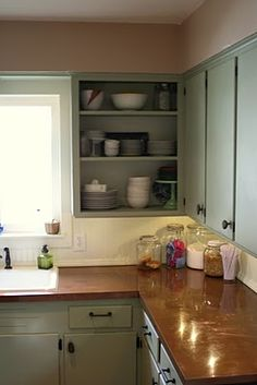 Patina copper countertops contrasted by simple minty green cupboards with black iron knobs & pulls.
