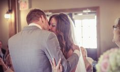 Bride and groom's first kiss with audience behind | Vintage wedding photography | www.newvintagemedia.ca
