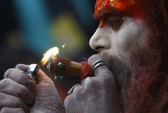 A Hindu holy man, or sadhu, smokes marijuana on a chillum (pipe) at the premises of Pashupatinath Temple during the Shivaratri festival in Kathmandu February 27, 2014. Hindu holy men from Nepal and India come to this temple to take part in the Shivaratri festival. Celebrated by Hindu devotees all over the world, Shivaratri is dedicated to Lord Shiva, and holy men mark the occasion by praying, smoking marijuana or smearing their bodies with ashes. (Photo by Navesh Chitrakar/Reuters)
