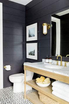Bathroom with black paneled walls, a gold sconce, art, and printed tile floors