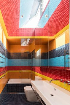 This modern bathroom features brightly colored tiles in bold stripes, that cover the floor, walls and ceiling. #ColorfulBathroom #BoldStripes #TileIdeas #BathroomDesign #Colorful #InteriorDesign