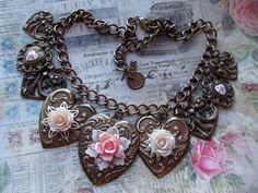 FUF 1/16/15 B'Sue chocolate ox hearts in man designs, with resin and vintage plastic roses, filigree and vintage Guilloche hearts. Vintage brass chain. MockiDesigns