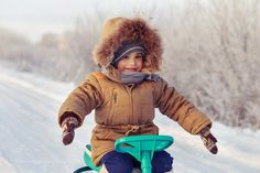 Little boy riding his kids snowmobile winter snow-covered road by dimkastepin