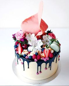 A vanilla layered buttercake with Swiss meringue buttercream topped with mixed berries, macarons, fresh flowers, a huge pink sail, toasted meringue and burgundy coloured pipings from Cakes by Cliff in Sydney, Australia