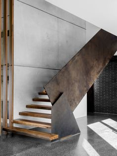Contemporary industrial timber staircase with rusted steel balustrade and concrete tilt-panel walls