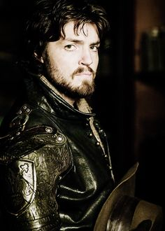 Athos. A brilliant swordsman, is the glue that binds the Musketeers together. His character commands respect. At first sight he can appear arrogant but his offhand manner disguises a deep capacity for friendship. He is wryly humorous and engaging but during bouts of solitary drinking he has the capacity to hit the self-destruct button. At these times, the bottled-up darkness from his past threatens to engulf him.