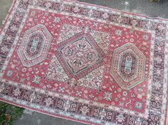 Featuring bold shades of red, this is a vintage Persian-style rug. Slightly worn condition but still beautiful for use. Great for a variety of home styles -- boho, mid century, rustic, etc.  CONDITION: The ends of the rug are very frayed (see close-up photos), and there are a few little creases in the edges. The rug is slightly darkened all over, but there are only a few minor stains throughout (see close-ups for worst spots).  MEASUREMENTS: 68 inches by 98 inches (just over 5.5 ft. by 8…