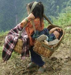 A child takes care of her sister and takes food from the mountain. Sapa, Vietnam:
