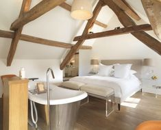 Bedroom with giant deep modern  cast iron bath tub heaven next to wood burning stove and cosy gigantic bed