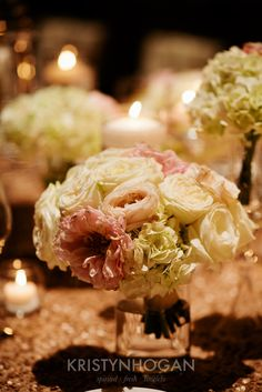 white and blush bouquets on reception table with candles