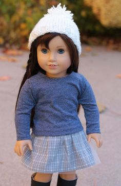 Four Piece outfit made to fit 18 inch dolls such as American Girl®  Outfit includes Light Grey Jacket Grey Blue Plaid Skirt Blue Heather Tee Shirt Creamy White Knit Hat  The unlined jacket is made from a textured twill in a pale grey. It features contoured waistband, front, back and sleeve seaming details. The asymmetrical front closes with black buttons and buttonon holes. The jacket is made from a Noodle Clothing pattern also available in my shop. In fact this is one of the cover outfits…