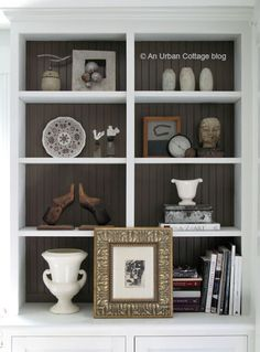 Lovely bookcase staging. White bookcase with dark painted beadboard background.