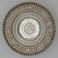 Silver flanged bowl; beaded rim; flange ornamented with foliage design in relief, including bunches of grapes, bird and rabbit; interior fluted, central medallion with lobed pattern. Condition shots for 'Buried treasure' exhibition.       Romano-British 4thC. | © The Trustees of the British Museum
