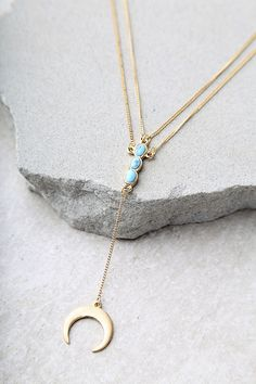 "Our intuition is telling us the Moonstruck Gold and Turquoise Layered Necklace is the next big thing! Layers of dainty gold chain with turquoise and crescent charms. Shortest chain measures measures 17"" long with a 3"" extender chain."