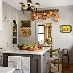 Vintage-Style | A small but efficient island holds refrigerator drawers and a bookcase for cookbooks. Painted deep gray to contrast with the lighter color of the cabinets and topped with marble, it feels vintage and authentic to the homes' architecture.