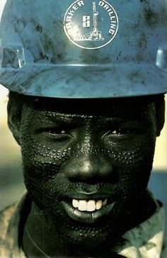 Nuer man wears a hard hat for his job on an oil rig in Sudan  National Geographic | May 1985