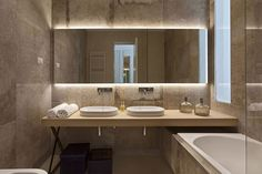 an exciting brown marble bathroom with simple twin washbowls and modern bathtub and frameless mirror also wall lamp