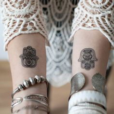 Two small hamsa hand tattoos with a very intricate design.
