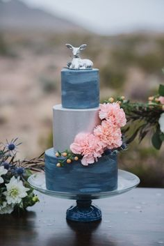 Las Vages bake shop Gimme Some Sugar designed this elegantly whimsical cake, which features two hand-painted stony-blue tiers and a silver metallic middle tier. | Photo by Rae Marshall