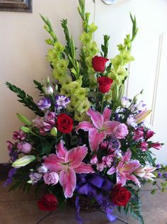 A line arrangement stargazers, alstroemerias, roses, status, gladiolus lisanthus mixed greens