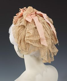 In the early 1880s the hair was dressed very simply and lay close to the head, with large curls worn low and the front waved or in a large knot on the crown and the front combed back. Young women wearing the fashionable hairstyle of the time were no longer wearing day caps. This cap would more likely have been worn by a married woman as part of her morning toilette. Met. ca 1880