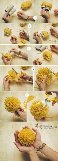 PASSO A PASSO 1. Primeiro vamos fazer o mini pompom. Pegue o garfo e enrole a lã mais grossa envolta, como na imagem. Quanto mais voltas no garfo, mais fofinho fica seu pompom. Quando terminar corte. 2. Pegue a linha mais final e corte um pedaço dela. Passe no meio do garfo, de forma que abrace a lã enrolada e dê um nó. 3. Vire e dê mais um nós do outro lado. Retire do garfo. 4. Pegue a tesoura e corte os dois lados. Seu pompom já está tomando forma. 5. Apare as pontinhas para que seu mini…