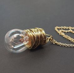 This found object necklace is made from a vintage auto light bulb wrapped in brass wire. The light bulb pendant is hung from a 20 brass colored chain. The
