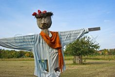 A beautiful scarecrow, nicely covered in colorful old cloth and scarf, standing in a field in summer time