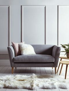 The Timsbury two seater sofa is by Cox and Cox. This occasional sofa is handmade with a solid birch and beech hardwood frame and is finished in a soft grey flatweave cotton material.