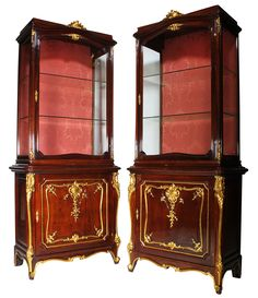 A Fine Pair of French 19th-20th Century Louis XV Style Mahogany and Parcel-Gilt-Wood Carved Vitrines by Mâison de Forest, Paris. Each two-corps cabinet crowned with a carved parcel-giltwood shell above a single door vitrine with two glass shelves. The lower storage compartment with single carved wood shelf and a parcel-giltwood carved door decorated with shells, flowers, leaves and acorns, all within a gilt trim. The corners with parcel-gilt carved wood shells and trim ending on cabriolet…
