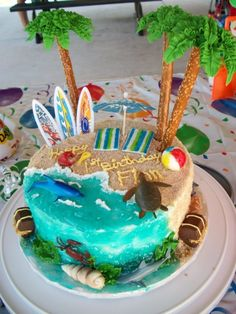 Good use of the plastic surfboards buttercream w/sifted brown sugar for sand, royal icing palms piped over the bottom of small bowls, fondant towels and beach ball painted w/food writer, fondant pail and shovel handle,hersey nuggets treasure chests. Sea Creatures are plastic. Drink umbrella. Cut sour green-apple candy straws in half crosswise. Use a paring knife or scissors to make several slits 3/4 of the way down on the halved candy straw. Insert the solid end into a pirouette cookie