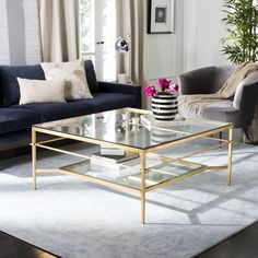 null Rounding out your decor while keeping beverages, remotes, and more at arm's reach, coffee tables are essential in any home. Anchor your living room look with some contemporary style using this understated coffee table as your base. Crafted from iron, it boasts a glossy finish and strikes a square silhouette. It's tabletop and lower shelf both sport a glass surface, so it's easy to keep clean. Base Color: Gold Leaf/Glass