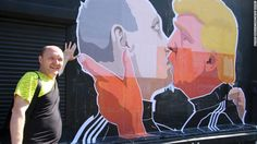 A man poses next to a mural on the wall of Keule Ruke depicting U.S. Presidential hopeful Donald Trump and Russian President Vladimir Putin greeting each other with a kiss in the Lithuanian capital of Vilnius on May 13, 2016.
