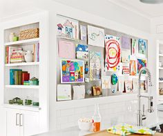 Create a Display Wall . Here, a slim piece of steel, framed by wide trim work, dresses up a long wall in the kitchen, allowing for  rotating display of your family's loves, passions, and interests - use magnets for easy changes of art, etc.