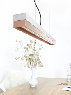[C1]copper    The rectangular pendant lamp [C1]copper is cast from a light gray concrete. It combines modern copper sheet with rough concrete into a