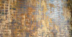 Faux brick wall using brick paneling, plaster, & mortar, along with a mix of glazes & washes