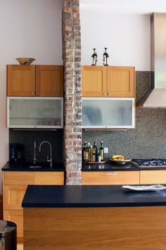 The original brownstone brick wall intersects the kitchen and defines where the original building ends, and the new addition begins.