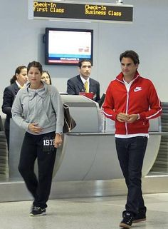 Roger Federer and wife Mirka. Pretty sure this photo is long ago, RF and family now use Net Jets etc (private jets)  They are about 3 feet apart so this photo is probably very early in relationship maybe around 2002. By 2003 Mirka was courtside all the time (when RF won his lst GS, Wimbledon)