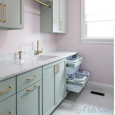 Pale pink walls and brass make for a great laundry room.