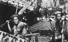 Two Dayak men of Borneo. Dude on the left wears a sheathed Mandau sword. The shield, Mandau scabbard and guy-on-the-right's sword are decorated with human hair. The Dayaks kicked a lot of Japanese butt in the jungle during WWII.