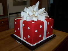 Special Birthday or promotion at work... this cake really is the present. Dark chocolate trim with red colored fondant decorated as polka-dot paper & topped with a large amazing white bow.