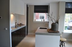 Handgeschilder zwarte keuken met zijdeglans witte stollen en een keramiek werkblad in betonlook.
