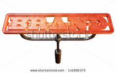 A metal cattle brand with the word brand as the marking area glowing red hot on an isolated background - stock photo
