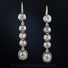Sparkling 1 & 1/2 inch long diamond earrings, crafted in platinum over 18 karat gold.These early-Art Deco dazzlers featrue 10 old mine-cut diamonds weighing 4.50 carats total, including two diamonds weighing one carat each at the bottom & two half-carat diamonds on top. Each bezel-set diamond floats inside a bright platinum frame. Lang Antiques $15,750