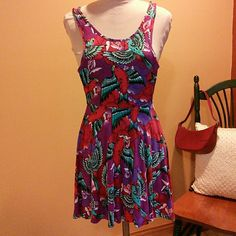 Tattoo Inspired Dress Tank dress with tattoo inspired print in colors of purple, red, turquoise, black and white. No tags but it was purchased at Fetish in Asbury Park, NJ. Waist is 24 inches, torso is 15 inches, skirt is 17 inches. Skater style. Dresses
