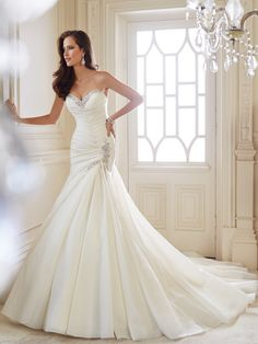 Y214462 - Trumpet wedding gown with chapel train, couture-inspired chevron pleating is the standout feature of this strapless crystal organza trumpet gown. The sweetheart neckline and side hip are trimmed with matching decedent crystal hand-beaded lace. Ginger also features a back corset partially concealed by matching crystal-beaded lace at the top of the chapel length train. Removable straps are included. Ivory, Diamond White, White